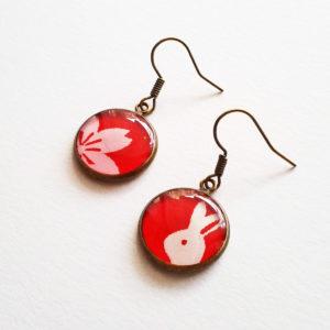 Akane, boucles d'oreilles courtes motif fleur de cerisier et lapin blanc sur fond rouge